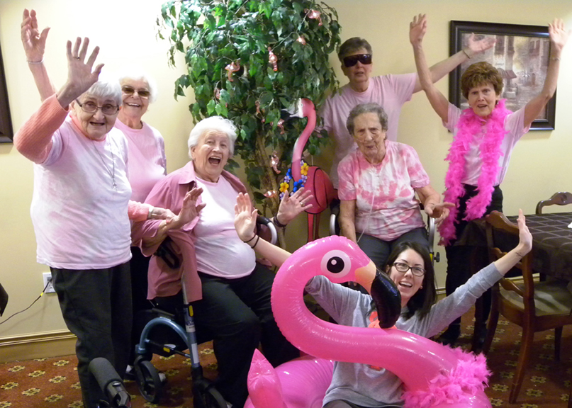 Team members and residents having a flamingo-themed party.